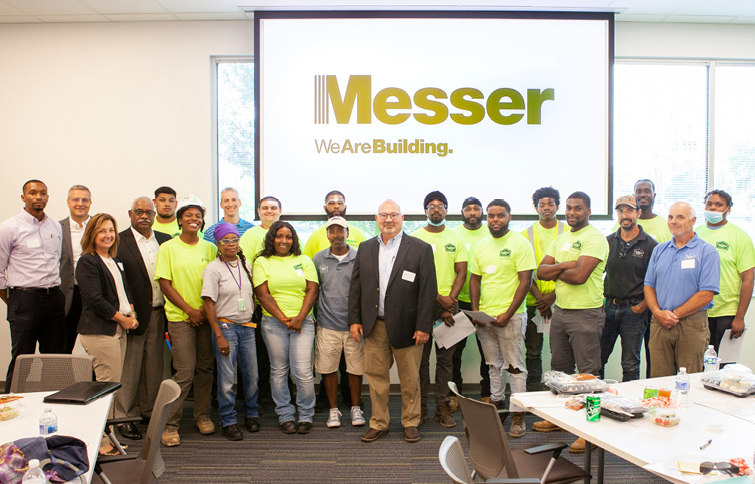People standing in front of Messer logo at UWDI graduation